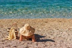 Beautiful female in the bikini and straw hat on the beach and sea background. Beautiful female in the bikini and straw hat on the beach and the sea background Stock Photo