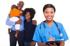 Black nurse family. Beautiful female black nurse with family patients on background Stock Image