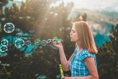 Beautiful female blowing bubbles at sunset stock photography
