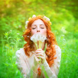 Beautiful female blowing on a dandelion flowers Royalty Free Stock Images