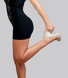 Long legs and high heels. Beautiful female body in high heels and short black skirt isolated on gray background Royalty Free Stock Photos
