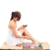 Beautiful female body legs with cosmetic container bowl and cream Stock Images