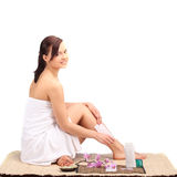 Beautiful female body legs with cosmetic container bowl and cream Royalty Free Stock Image