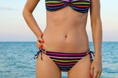 Beautiful female body in striped bikini. Beautiful shapely female torso in a striped bikini posing in front of the ocean Stock Image