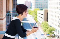 Beautiful female, businesswoman relaxing on a balcony on a sunny summer day,drinking red wine Stock Photos