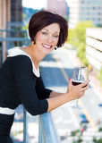 Beautiful female, businesswoman relaxing on a balcony on a sunny summer day,drinking red wine Royalty Free Stock Photo