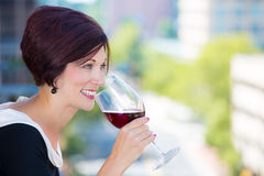 Beautiful female, businesswoman relaxing on a balcony on a sunny summer day,drinking red wine Stock Photo