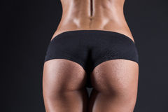 Beautiful female buttocks tight. Beautiful female tight buttocks on a black background Royalty Free Stock Photos
