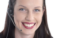 Close up front view, smiling beautiful female call center worker, telephone headset Royalty Free Stock Image