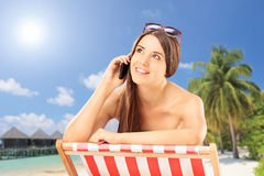 Beautiful female on a chair talking on a phone, on a beach Royalty Free Stock Images