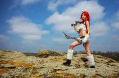 Beautiful female character with two swords on big stones. In mountain area. Fashion model girl cosplay character Royalty Free Stock Photos