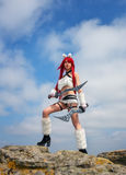 Beautiful female character with two swords on stones in moun Stock Image