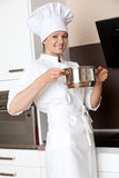 Female chef in white uniform cooking in kitchen Stock Photo