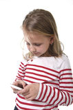 Beautiful female child with blond hair and blue eyes using mobile phone playing game Royalty Free Stock Image