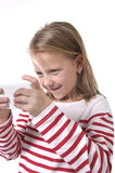 Beautiful female child with blond hair and blue eyes using mobile phone playing game Royalty Free Stock Photo