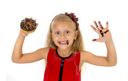 Beautiful female child with blue eyes in cute red dress eating chocolate donut with syrup stains Stock Photos