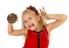 Beautiful female child with blue eyes in cute red dress eating chocolate donut with syrup stains Royalty Free Stock Photos