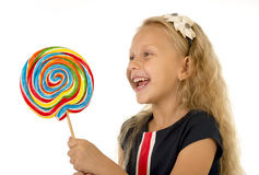 Beautiful female child with long blond hair holding huge spiral lollipop candy smiling happy Royalty Free Stock Image