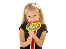 Beautiful female child with long blond hair holding huge spiral lollipop candy smiling happy Stock Images