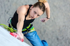 Beautiful female Climber moving up on vertical climbing Wall Stock Photography