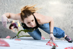 Beautiful female Climber moving up on vertical climbing Wall Stock Image