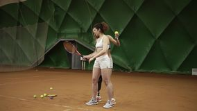 A beautiful female coach with a prosthesis on her leg shows her ward the nuances of the ball hitting in tennis standing. Behind her. Sports girls stock video