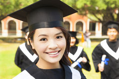 Beautiful female college graduate with classmates at ceremony Stock Image