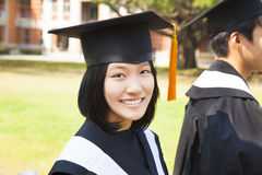 Beautiful female college graduate with classmates at ceremony Stock Photo