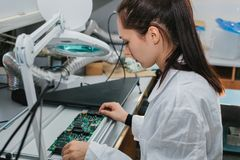 Beautiful female computer expert professional technician examining board computer in a laboratory in a factory. Troubleshooting. Technical support Royalty Free Stock Images