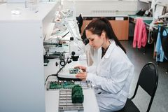 Beautiful female computer expert professional technician examining board computer in a laboratory in a factory. Troubleshooting. Technical support Royalty Free Stock Photography