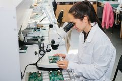 Beautiful female computer expert professional technician examining board computer in a laboratory in a factory. Troubleshooting. Technical support Stock Photo