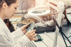 Beautiful female computer expert professional technician examining board computer in a laboratory in a factory Royalty Free Stock Image