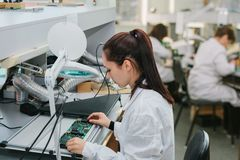 Beautiful female computer expert professional technician examining board computer in a laboratory in a factory. A female technician checks a computer board in a stock images