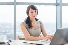 Beautiful female copywriter sitting in office, typing new article, working with text, using laptop at workplace. stock photos