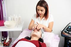 Beautiful female cosmetologist applying a facial mask to a female client in a beauty salon stock photography