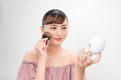Beautiful Female With Cushion Puff And Mirror Applying Makeup Powder Foundation.  royalty free stock photography