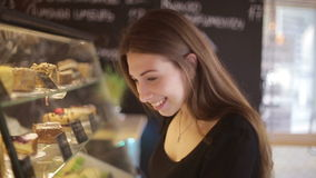 Beautiful female customer shopping showcase in a bakery store pointing at the dessert she is buying stock video footage