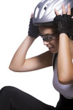 Beautiful female cyclist in professional equipment fixing helmet Stock Images