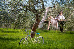 Beautiful female cyclist with retro bicycle in the spring garden Royalty Free Stock Photo