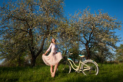 Beautiful female cyclist with retro bicycle in the spring garden Stock Photos