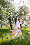 Beautiful female cyclist with retro bicycle in the spring garden Stock Photo