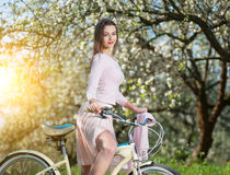 Beautiful female cyclist with retro bicycle in the spring garden Stock Photography