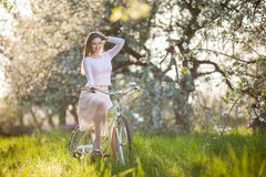 Beautiful female cyclist with retro bicycle in the spring garden Royalty Free Stock Images