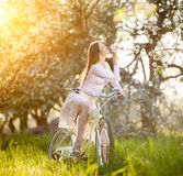 Beautiful female cyclist with retro bicycle in the spring garden Royalty Free Stock Photos