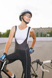 Beautiful female cyclist taking a break outdoors. Royalty Free Stock Photos
