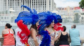Beautiful female dancers wearing a costume and a head dress with red and blue feathers, making photo next to Bellagio hotel. Las royalty free stock photography