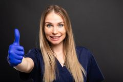 Beautiful female dentist wearing scrubs showing thumb up. Beautiful female dentist wearing scrubs showing up down on black background with copyspace advertising Stock Photo