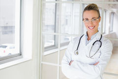Beautiful female doctor with arms crossed in hospital Royalty Free Stock Photos