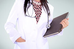 Beautiful female doctor carrying a notebook Royalty Free Stock Image