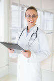 Beautiful female doctor with clipboard in hospital Royalty Free Stock Photography